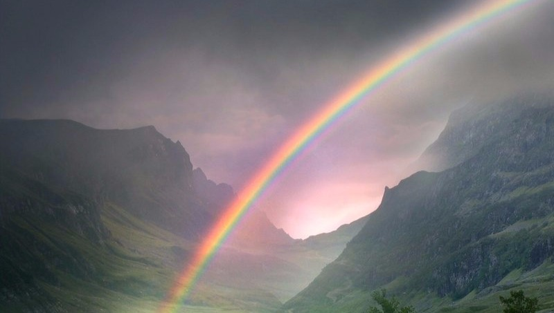 Rainbow over a misty valley on a grey day